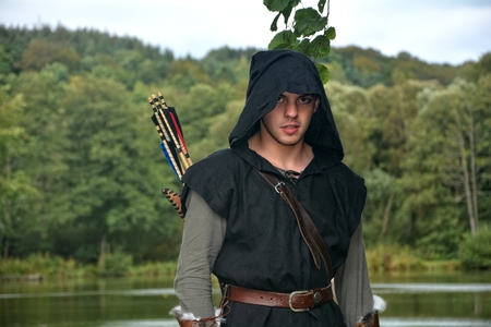 Medieval archer with black hood and colored arrows in the quiver stands before a lake and looks forwards Stock Photo