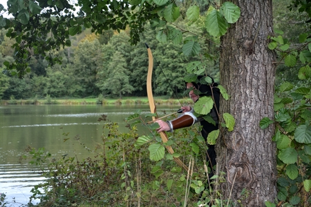 middle ages boat: Medieval archer with black hood stands hidden behind tree in the lake with tense curve