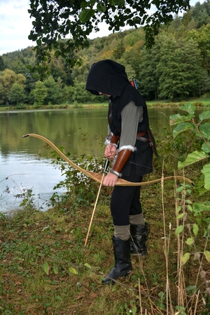 Medieval archer with black hood stands with tense curve and with arrows in the lake