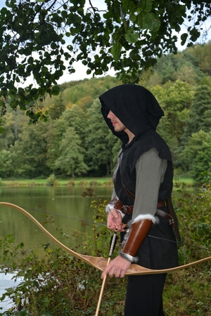 middle ages boat: Medieval archer with black hood stands with tense curve and with arrows in the lake