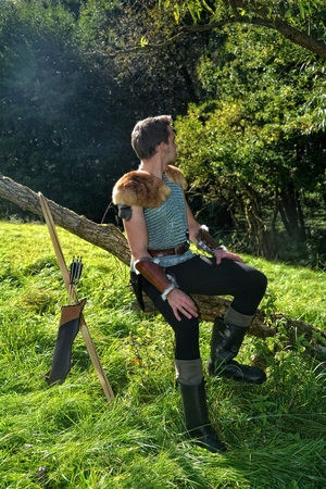 Young Medieval dressed man, sits on branch, arms on legs and looks to the back, arrow and curve stands besides Stock Photo