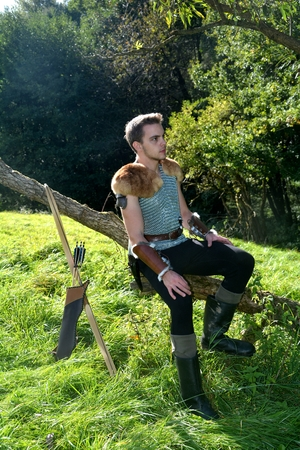 Young Medieval dressed man, sits on branch, arms on legs and looks aside, arrow and curve stands besides Stock Photo