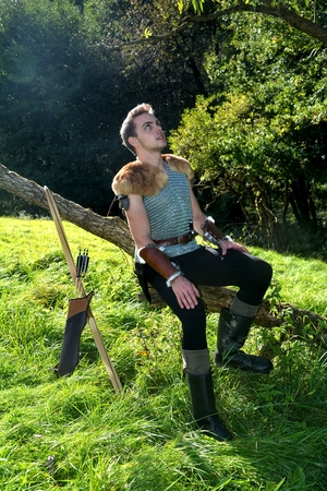 Young Medieval dressed man, sits on branch, arms on legs and looks upwards, arrow and curve stands besides