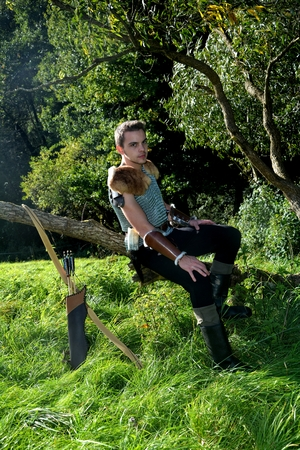 Young Medieval dressed man, sits on branch, arms on legs and looks forwards, arrow and curve stands besides Stock Photo