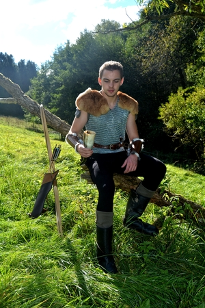 Young medieval archer with chain shirt sits on branch in the nature in the sunlight, drinking horn in the hand, arrow and curve stands besides