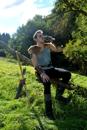 Young Medieval dressed man, sits on branch, drinks from drinking horn. Eyes open, arrow and curve stands besides