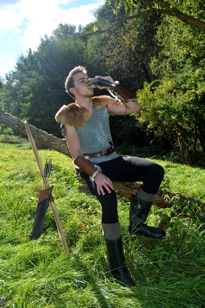 Young Medieval dressed man, sits on branch, drinks from drinking horn. Eyes closed, arrow and curve stands besides Stock Photo