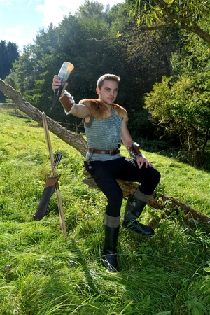 Young Medieval dressed man, holds drinking horn high in the hand and sits on branch in the nature