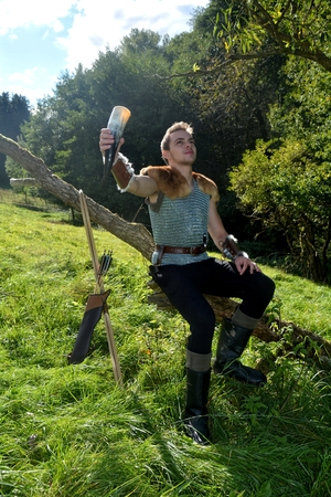 Young Medieval dressed man, holds drinking horn high in the hand, looks upwards and sits on branch in the nature
