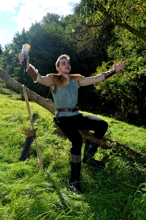 Young Medieval dressed one man, holds drinking horn in hand, Both arms stretched out and sits on branch in the nature