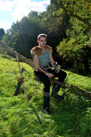 Young Medieval dressed man, holds drinking horn high in the hand, looks forwards and sits on branch in the nature