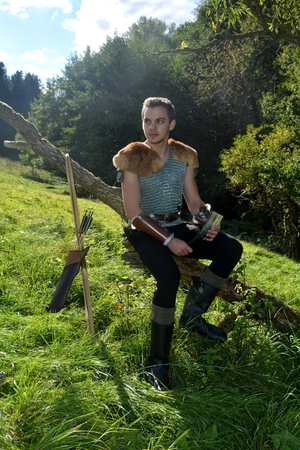 Young Medieval dressed man, holds drinking horn in the hand and sits on branch in the nature