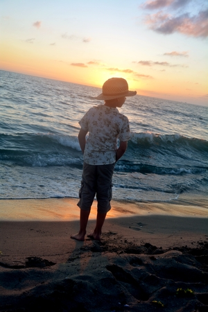 Small boy stands on the beach at the sundown, hands in the trouser pockets and looks aside