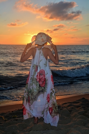 Girls in the long dress and holds with Both Hands care on the head and stands by the sea beach at the sundown, with look as the sun, the sun headcovers Stock Photo