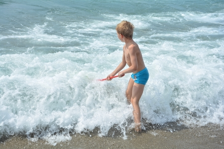 fishingnet: Small blond boy with blue swimming trunks stands with a fishing-net Directly in the sea - wave