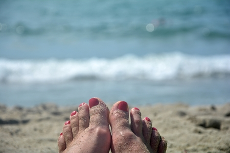 foci: Sandy feet with red toenails on the beach with blurred sea in the background Stock Photo