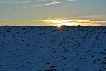 beaming: Stubble field in the snow, at sunrise behind the hills