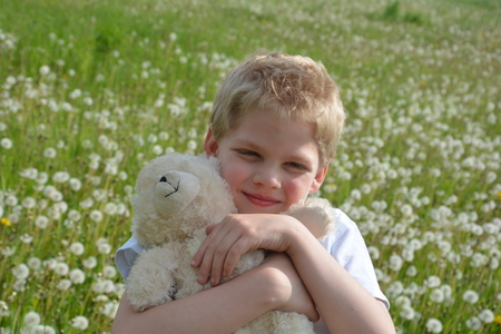 Small blond boy on meadow with puffs flowers, white teddy bear holds Firmly in the arm and looks forwards