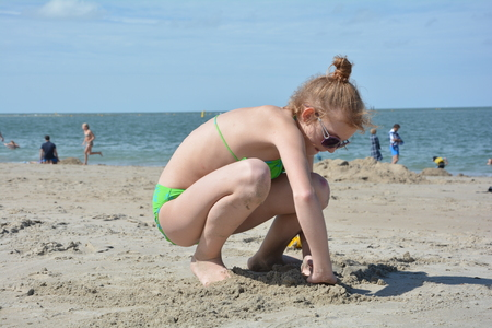 Girl digs her hands on the sandy beach before the sea