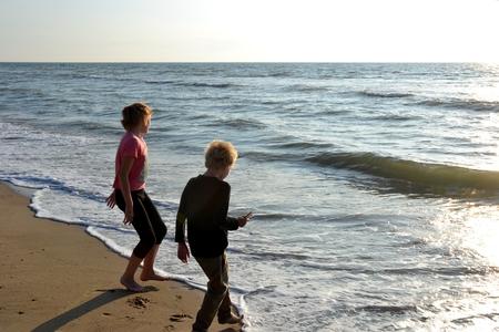 Zwei Kinder spielen am Sandstrand mit den Wellen am Meer
