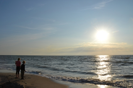 Two children stood at the sundown on the beach and look to the sea Stock Photo