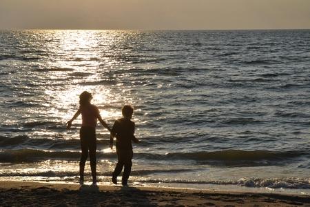 Two children stood at the sundown on the beach