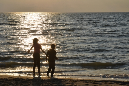 Two children stood at the sundown on the beach