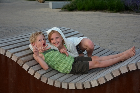 Two children sit on corrugated bench and make amusing movement of the hand