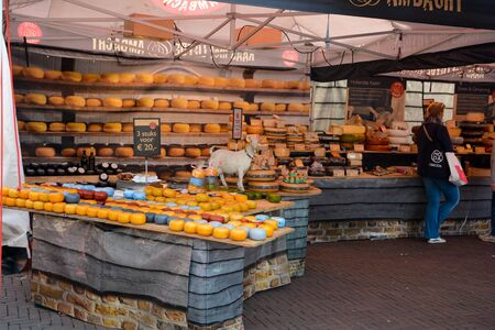 Sales booth with many different types of cheese in Middelburg, the Netherlands on August 12, 2017, with a woman