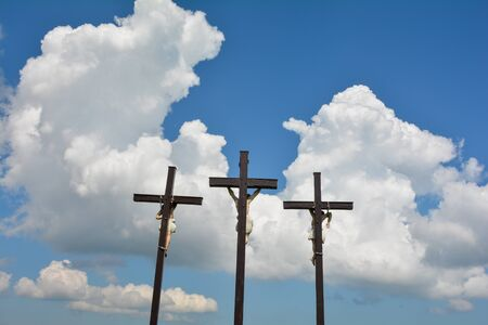 Three large crosses in front of white clouds with a blue sky