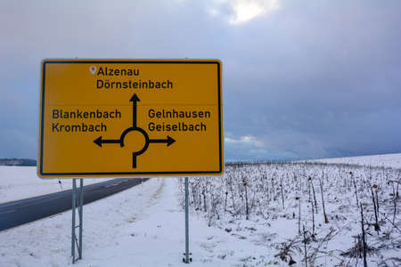 Street sign for a roundabout for various locations in Bavaria, Germany, in winter with snow and copy space