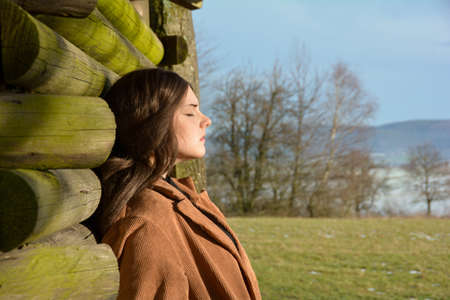 Young woman from the side, with light brown coat, leaning against a wooden hut, with a serious expression on her face and closed eyes, enjoying the sun, in green nature