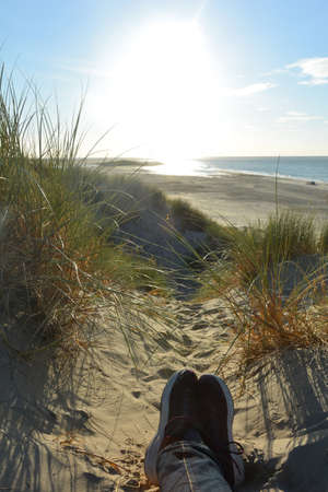 Resting between the dunes, lying on the beach with sneakers, with a view of the sea on the North Sea coast in the Netherlands with sun Banco de Imagens