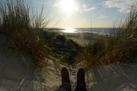 Resting between the dunes, lying on the beach with sneakers, with a view of the sea on the North Sea coast in the Netherlands