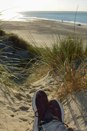 Resting between the dunes, lying on the beach with sneakers, with a view of the sea on the North Sea coast in the Netherlands in sunlight