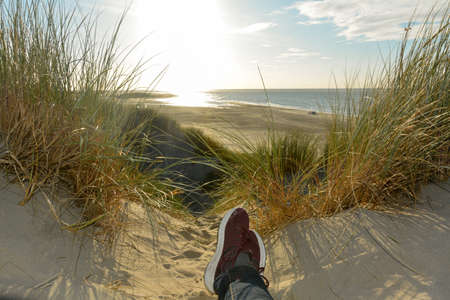 Resting between the dunes, lying on the beach with sneakers, with a view of the sea on the North Sea coast in the Netherlands with sun Stockfoto