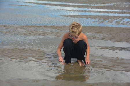 A boy is on the beach at low tide, looking for small fish in the shallow water
