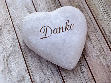Stone heart on a wooden background with german text Standard-Bild