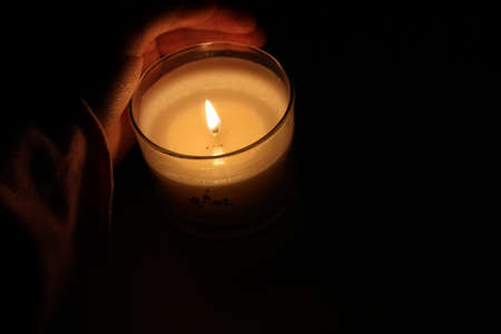 A hand, partially covered with a long, pink sleeve, wraps itself around a warm candle