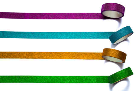 Four colorful rolls of washi tape unrolling horizontally on a white piece of paper. Selective focus