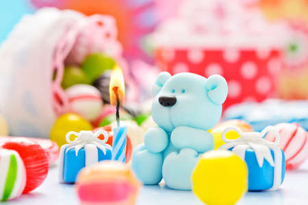 little sugar teddy with a candle and candies photo