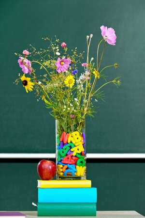 flowers in a vase decorated with alphabetical letters with an apple on a teachers desk in front of a board photo