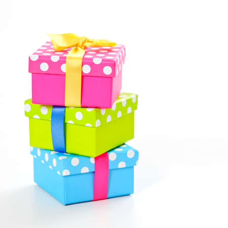 three colorful boxes with white dots and bow on white surface Stock Photo