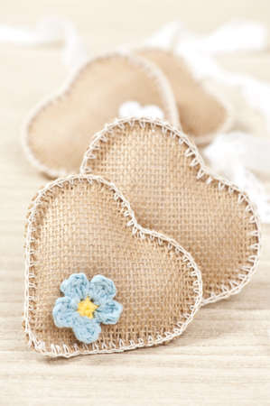 soft fabric hearts, decorated with chrochet flower on woodn surface