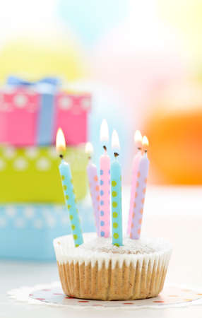 little cupcake with candles, in the backround some presents and balloons photo