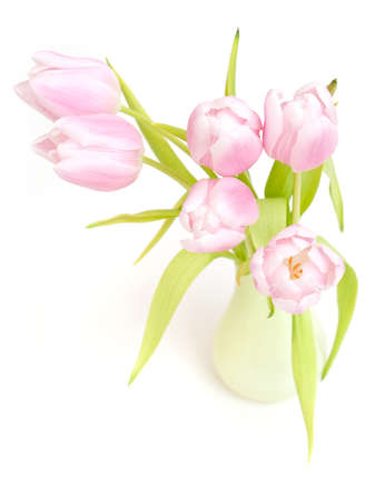 pink tulips in a green vase on white surface