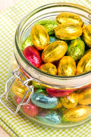chocolate eggs wrapped in colorful metal foil in a jar