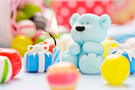 baby shower: little sugar teddy with sweets and candle Stock Photo