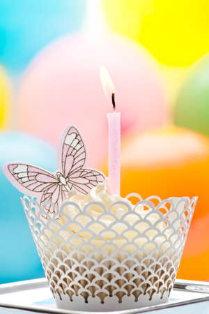 a cupcake, decorated with a butterfly, cream and a candle