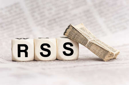 woodn dice depicting the letters RSS, with a stack of newspapers leaning on a dice photo